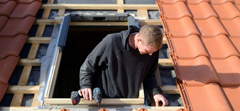 freundlicher Dachdecker Facharbeiter am Haus: Dachdecker Fenster einbauen im Eigenheim mit rotem Dachziegel