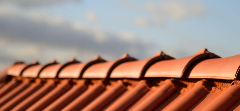 Dächer vom Dachdecker mit rotem Dachziegel Dachfirst. Dachpfannen auf Stadt Haus Neubau mit Abendrot Himmel im Hintergrund.