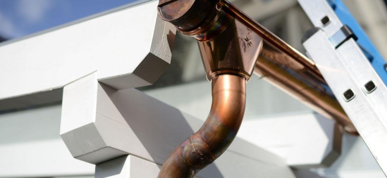 Klempner Arbeit Durchmesser 100mm. Neue Kupfer Dachrinne als Entwässerung am Flachdach mit Stutzen und Bogen